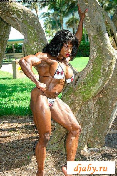 Зажигательная спортсменка в бикини играет мускулами
