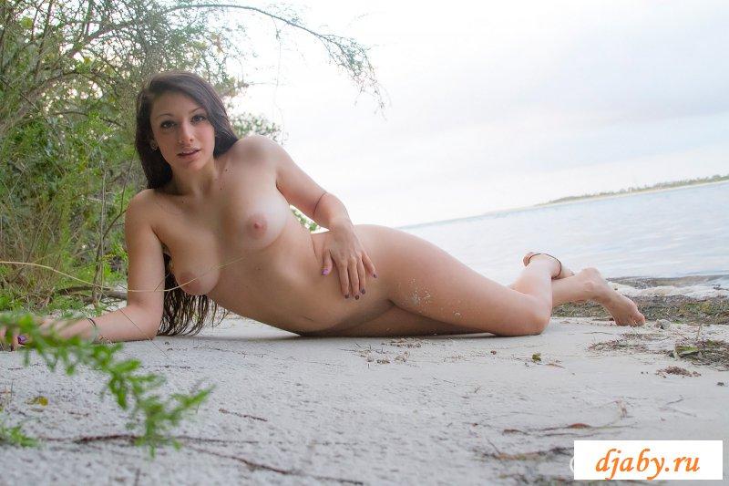 Обнаженная на тропическом острове без лифчика лежит на песке