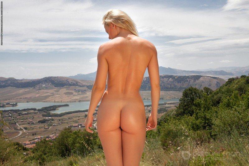 Обнаженная туристка позирует на природе