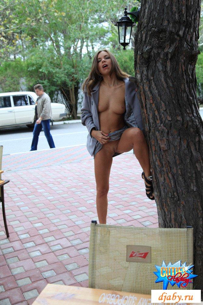 Молодая девушка эксгибиционистка с голым телом возле кафе